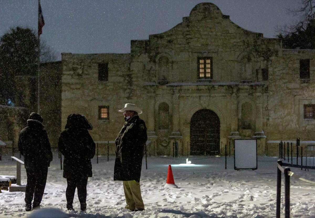 An Alamo security guard talks early Monday morning, Feb. 15, 2021 with people coming to look at the blanket of snow covering the Alamo. The National Weather Service reported Tuesday morning San Antonio and surrounding areas saw 3-5 inches of snow and some pockets of the forecast area saw 6-7 inches of snow. The Electric Reliability Council of Texas (ERCOT) has also declared the highest level of energy emergency and is requiring rolling blackouts throughout Texas. The National Weather Service reports the areas temperatures are the coldest since 1989.