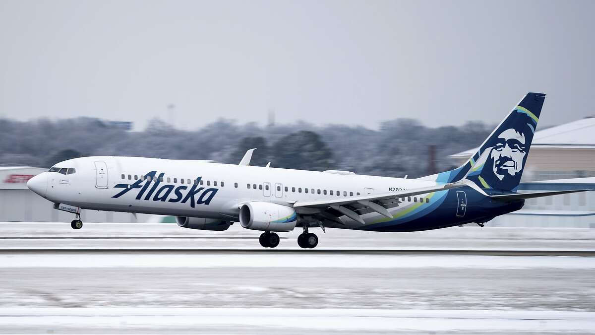 FILE -- An Alaska Airlines plane lands at Nashville International Airport in Nashville, Tenn., Tuesday, Feb. 16, 2021. Light snow continued to fall on Tuesday after a winter storm covered the Nashville area with freezing rain, sleet, and snow on Monday. (Andrew Nelles/The Tennessean via AP)