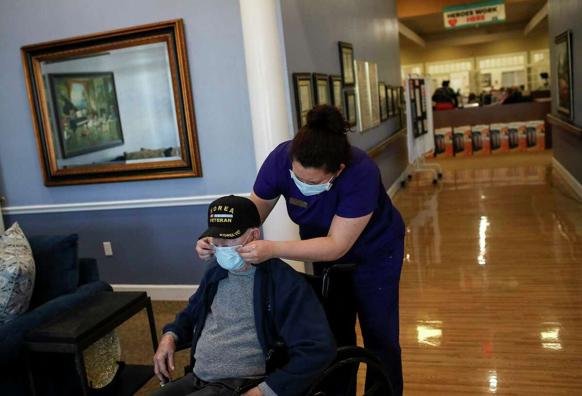 Erika Parrish, an administrator, helps adjust the mask on Wilbert Jacoby on Thursday, Feb. 18, 2021, at Bayou Pines Care Center in La Marque.