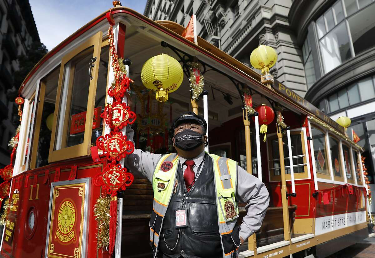 Cable car operator Val Lupiz stands outside of a cable car adorned in Lunar New Year decorations at Powell and Market streets, placed for photo opportunities.
