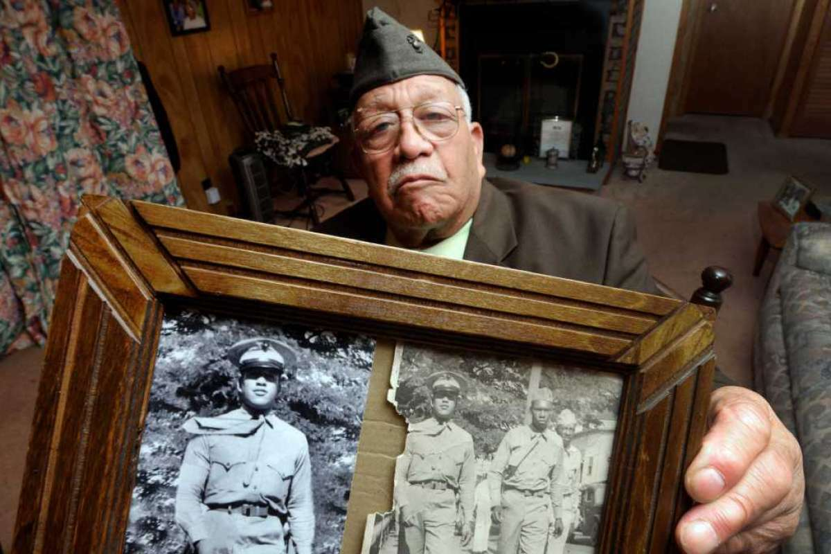 """World War II veteran Ambrose """"Cowboy"""" Anderson Jr. holds a photo from 1944, when he was a 18-year-old United States Marine, at his home in Gloversville, NY Thursday, Nov.10, 2011."""