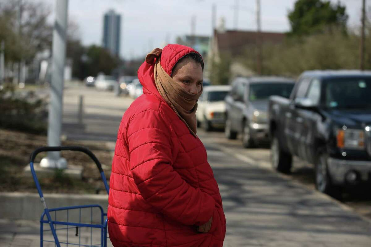 Cristina pasten waits in the 40-degree weather to wait for a water distribution because of the boil water order and low water pressure at Emancipation Park Thursday, Feb. 18, 2021, in Houston. U.S. Rep. Sheila Jackson Lee worked with National Association of Christian Churches to get the donated water for people at several distribution sites.