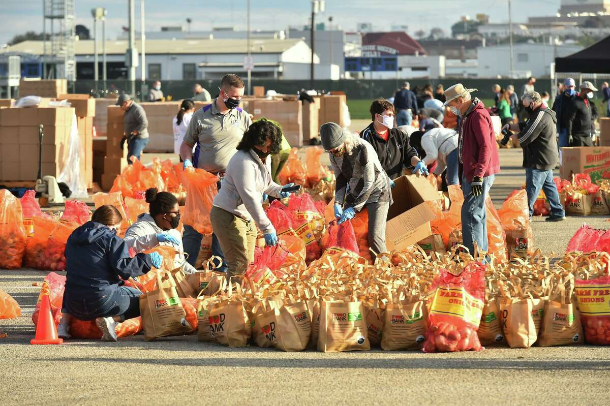 Volunteers prepare food bags during a San Antonio Food Bank mega distribution at Gustafson Stadium in January. Volunteers are needed for seven similar distributions this weekend to help people who have run out of food during the winter storm.