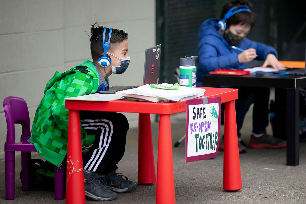 H. Suchovsky, 8, (left) and Evan Carnicelli, 7, sit side by side while attending class on their computer alongside fellow students at Midtown Terrace Park across the street from Clarendon Elementary School in San Francisco, Calif. Thursday, February 18, 2021 to participate in a