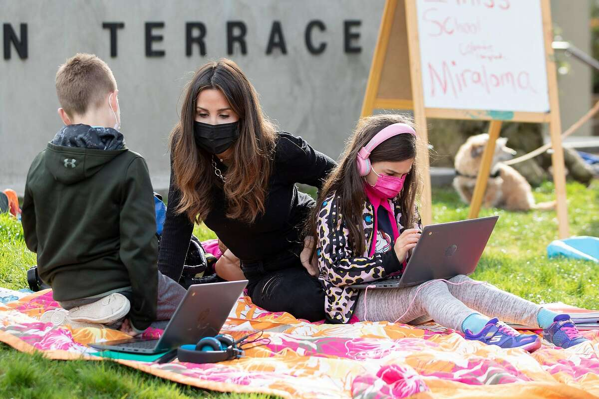 Sarah Swanson (center) helps her son, Hayes, 9, and daughter Larkin, 7, with their class connection while gathered with fellow students at Midtown Terrace Park across the street from Clarendon Elementary School in San Francisco, Calif. Thursday, February 18, 2021 to participate in a