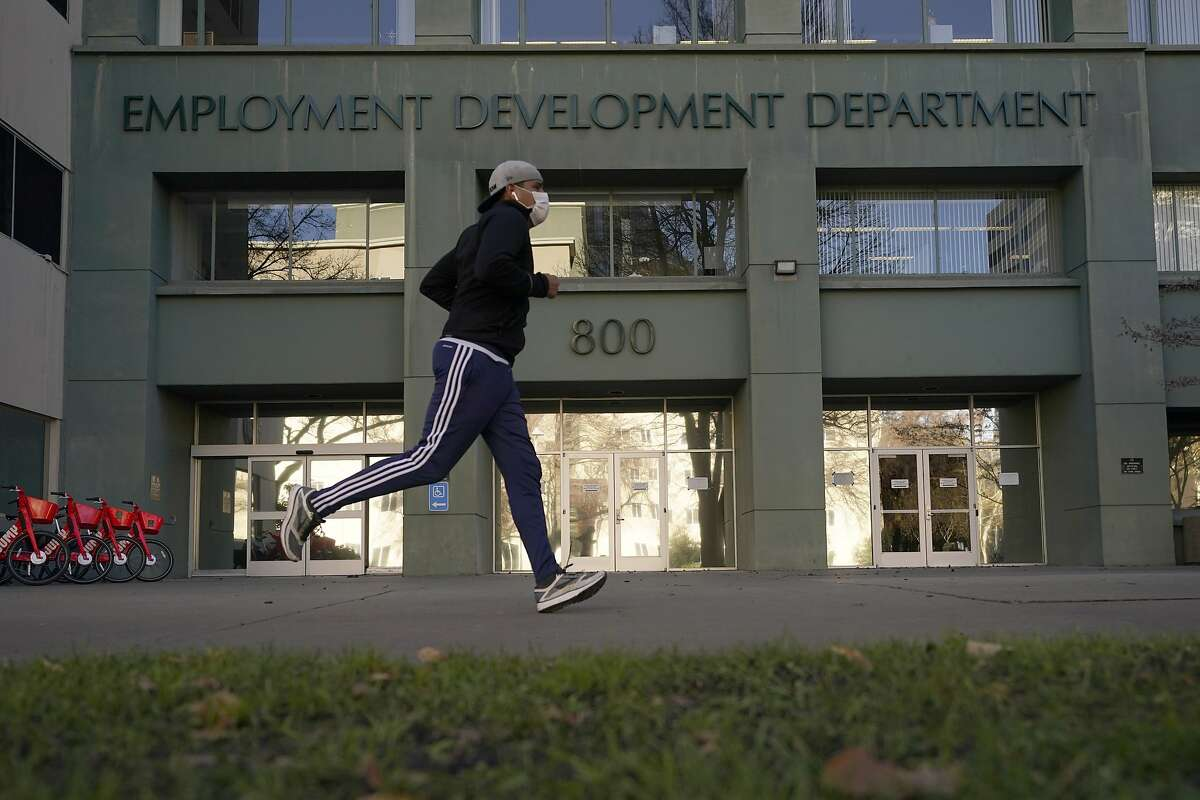 A runner passes the office of the California Employment Development Department in Sacramento in December.