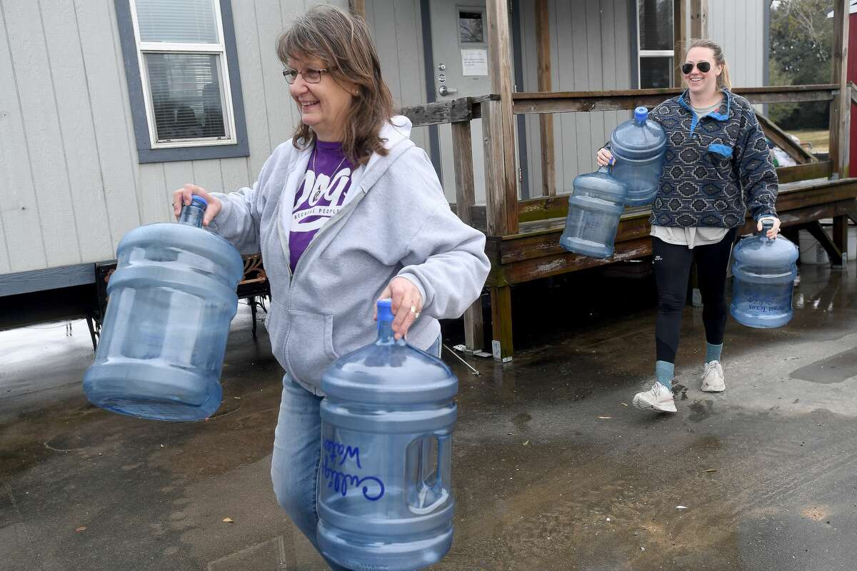 Shelter Manager Dee Dee Goode (left) helps Monica Lee carry empty jugs to her car at the Humane Society of Southeast Texas, which has been without water since Monday. The shelter has been reaching out through social media for donations to help provide drinking water for the animals, as well as water to clean. Lee, a former employee who continues helping whenever needed, has a well system of purified water and has been drawing from it to help amid the water crisis. Photo made Thursday, February 18, 2021 Kim Brent/The Enterprise