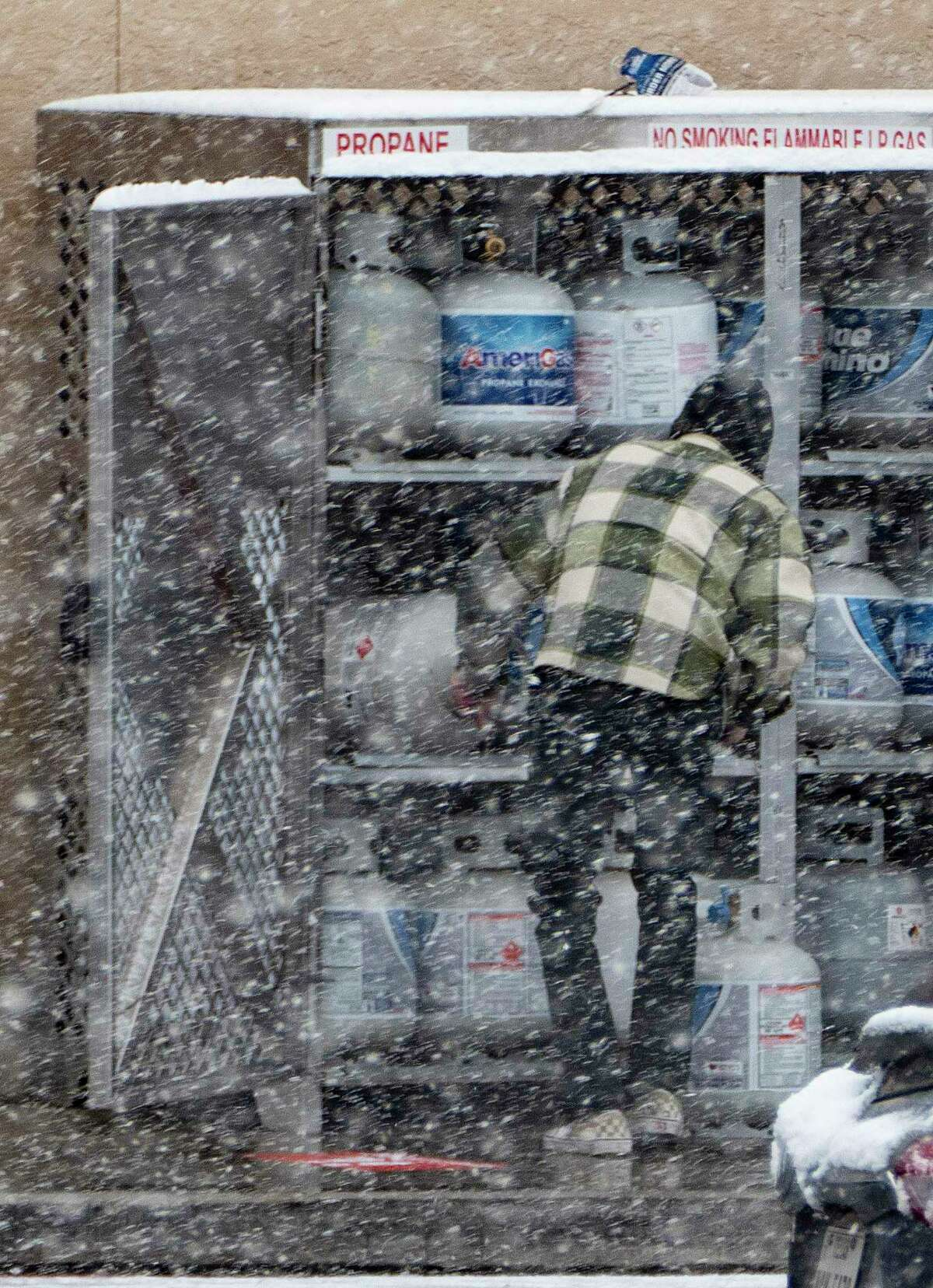 A man buys propane at the H-E-B at West Avenue and Blanco Road as a brisk snow falls on Thursday morning, Feb. 18, 2021.