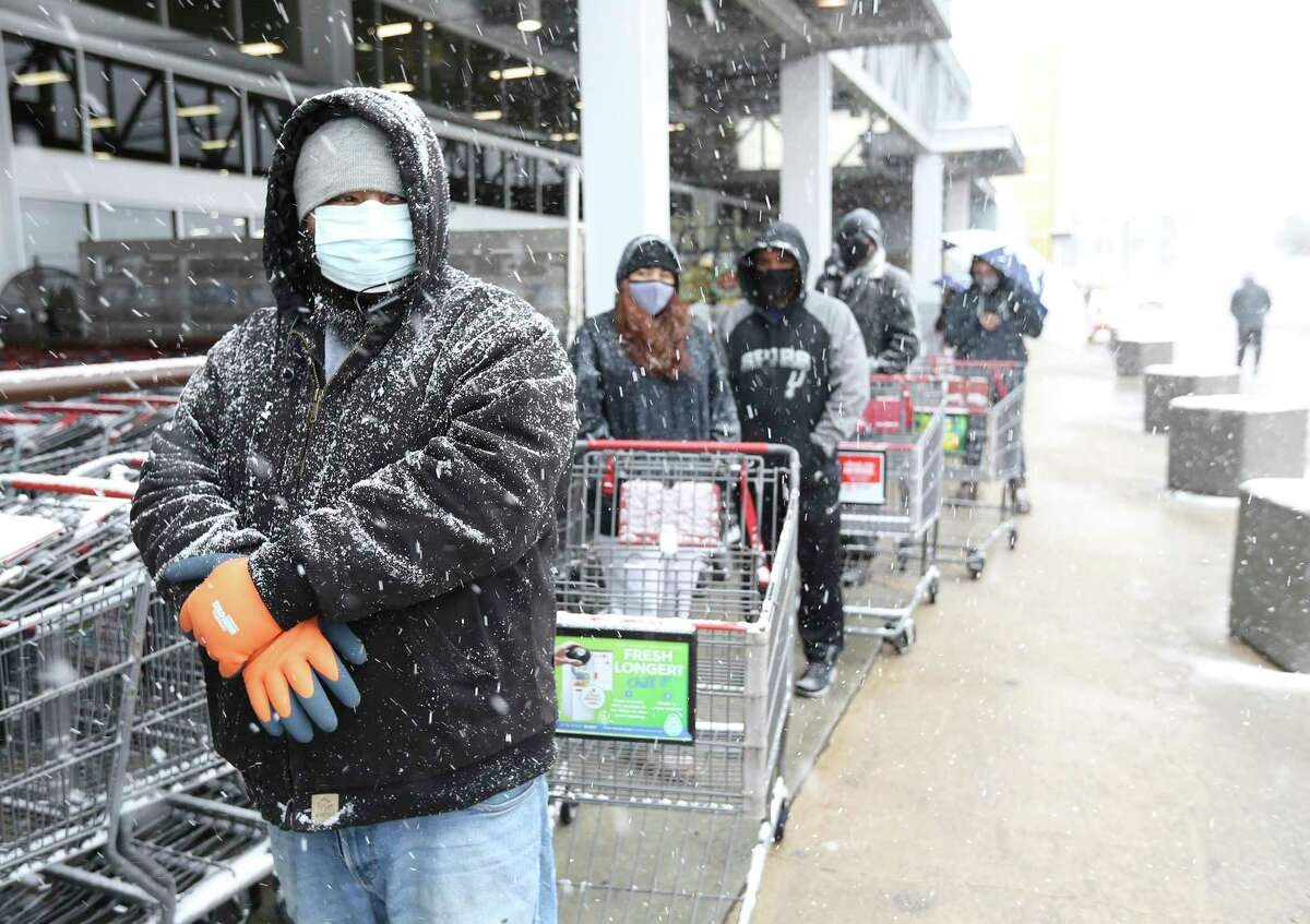 Alex Vega (left) waits with others to shop the HEB at Wurzbach Road during another day of snow fall in San Antonio on Thursday, Feb 18, 2021. Items like milk, eggs and meats were not available and water was limited.