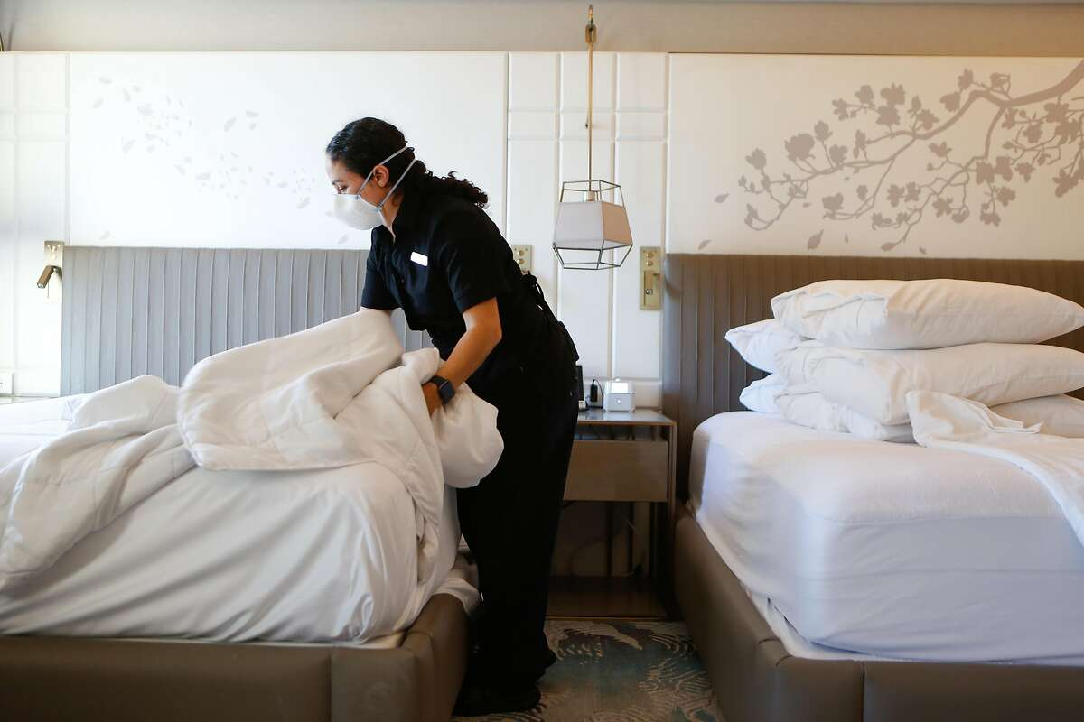Housekeeper Brenda Vallejo makes a bed in one of the few used rooms at Hotel Nikko in San Francisco in November.