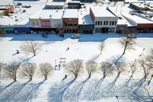 A combination of snow and ice blankets a mostly empty downtown Cleveland, Mississippi, on Feb. 16.