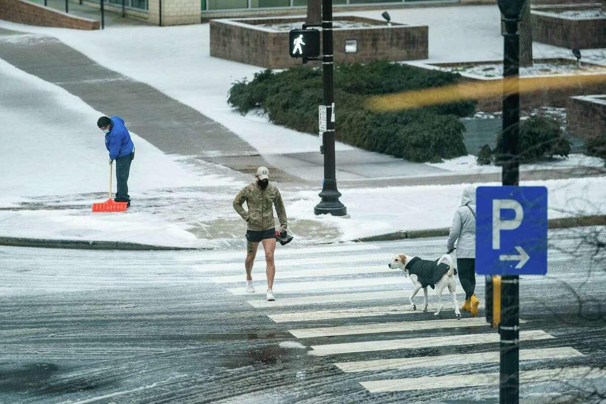 A man shovels a sidewalk as a pedestrian walks along Wilson Blvd. in Arlington, Va., Feb. 18, 2021.