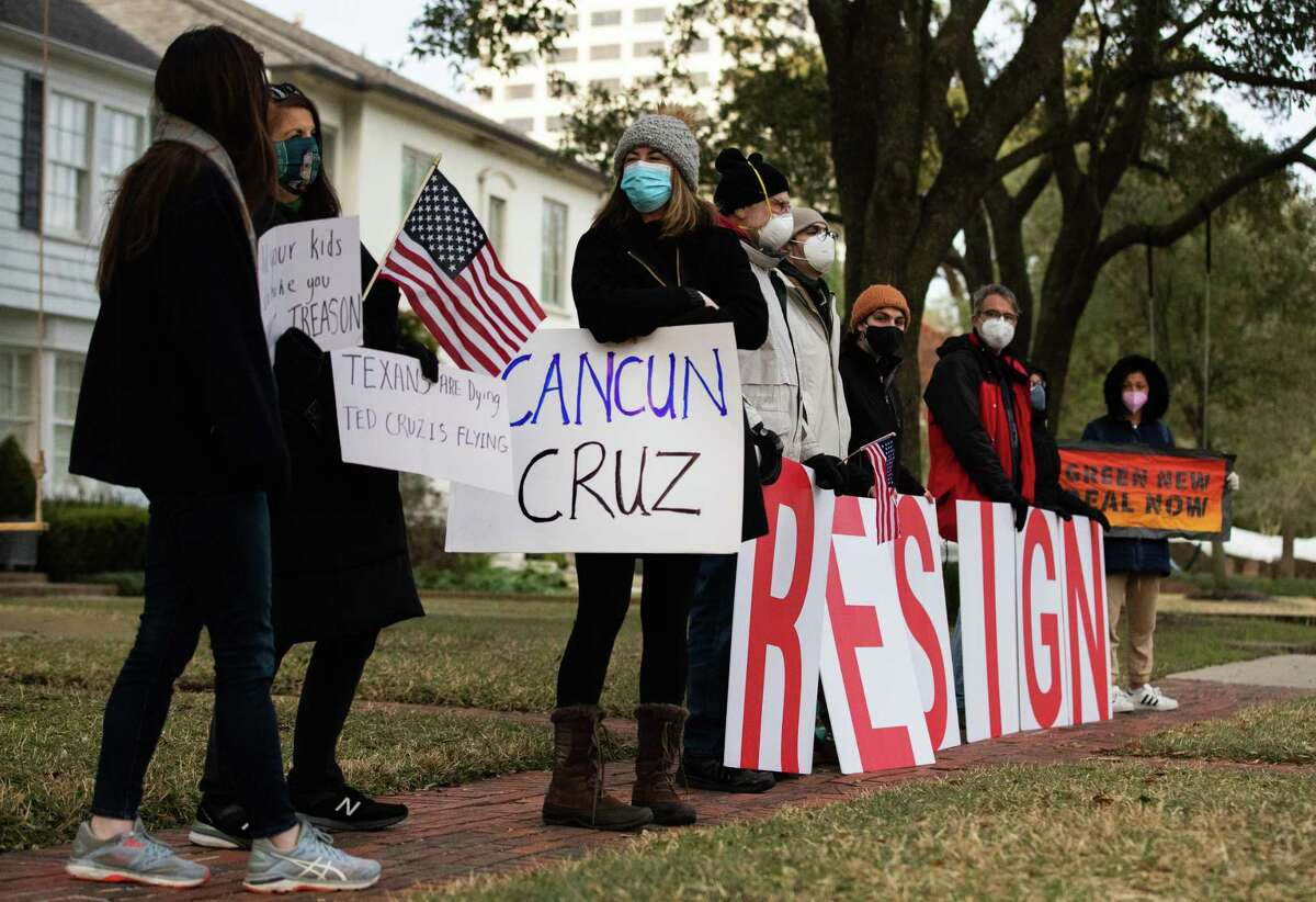Demonstrators stand in front of U.S. Senator Ted Cruz's home demanding his resignation, Thursday, Feb. 18, 2021, in Houston. The senator has been criticized from flying to Cancún with his family while the state is in crisis because of cold temperatures.