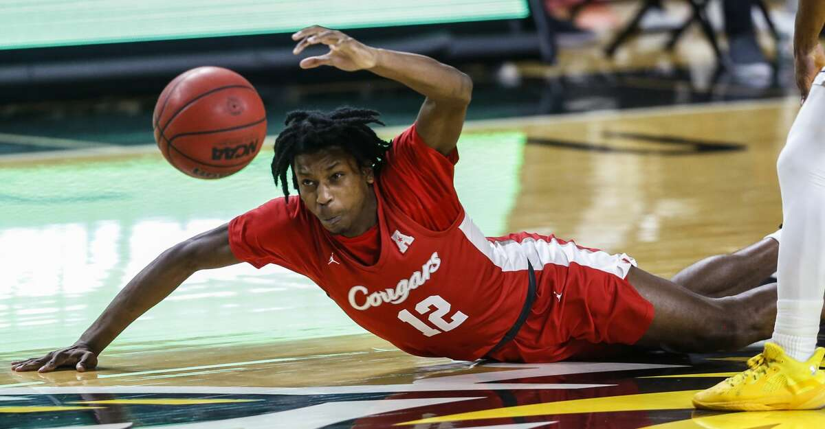 Houston's Tramon Mark falls to court while the chasing the ball next to Wichita State's Ricky Council, right, during the first half of an NCAA college basketball game Thursday, Feb. 18, 2021, in Wichita, Kan. (Travis Heying/The Wichita Eagle via AP)