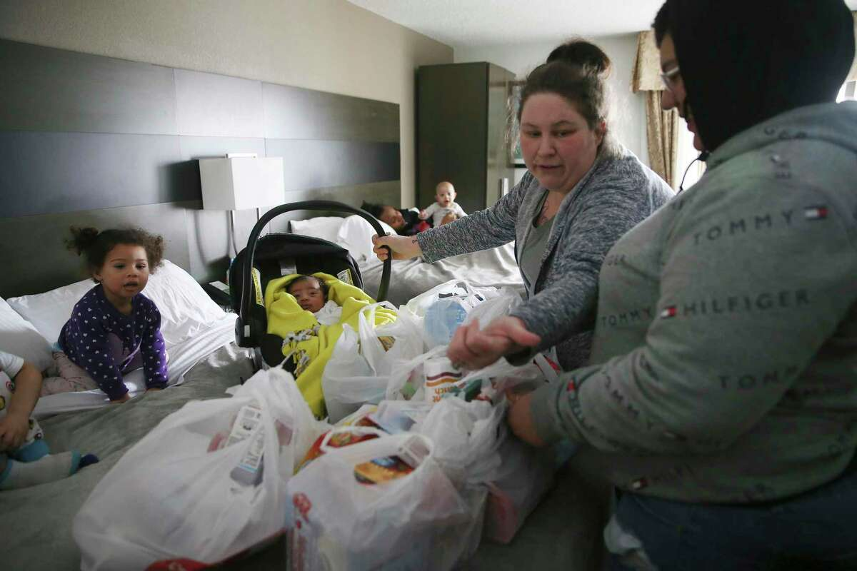 Brandy Robinson, 36, second from right, arrives back at their hotel room after a grocery run with her daughter, Cierra Arceneaux, 18, right, on Feb. 18, 2021. The family had to evacuate their apartment after it flooded due to a broken line to the water heater during the extreme cold spell.