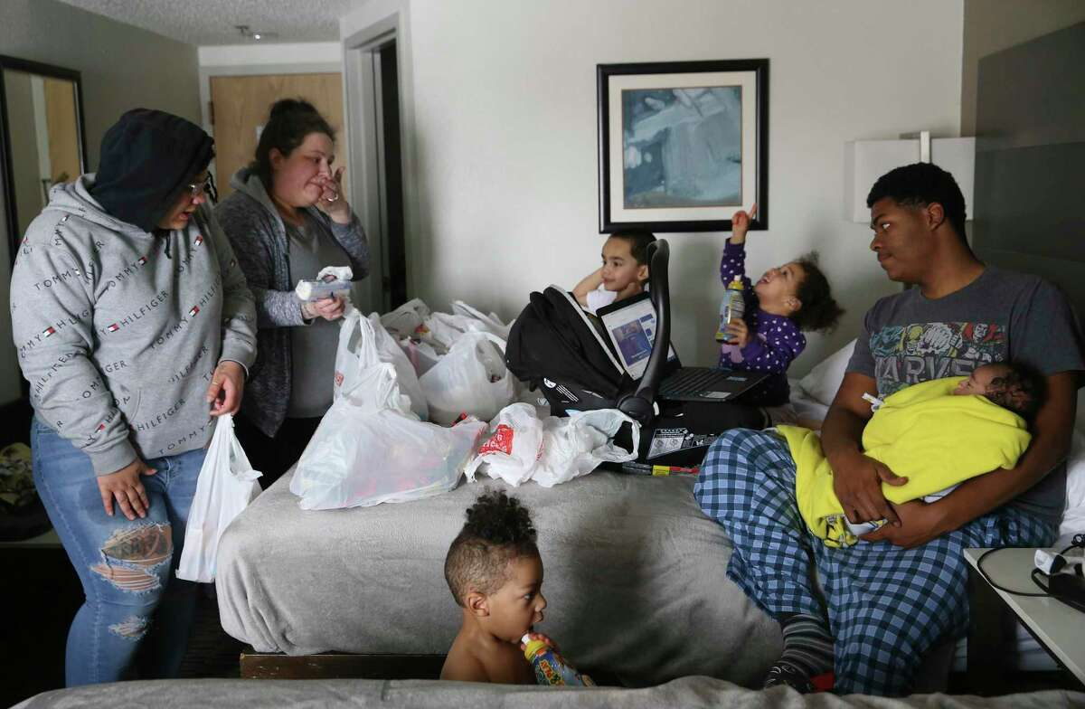 Brandy Robinson, 36, second from left, brings groceries to her family taking refuge at the Best Western Hotel off Loop 410 on Feb. 18, 2021. Their Seven Oaks Apartment unit flooded when a pipe leading to the water heater burst on Monday. With her are her daughter, Cierra Arceneaux, 18, left, and the daughter's boyfriend, Marquez Holmes, 18, right, holding their 2-month-old son, Legend. The couple's first born, Da'Mir Holmes, 2, plays between the beds. In the background are Robinson's son, Moses Delagarza, 1, and Addilynn Houston, 1, whose mother is also staying with them in the room.