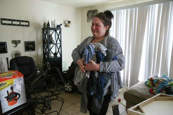 At the thought of losing mostly everything she owned, Brandy Robinson, 36, breaks down in the living room of her Seven Oaks Apartments unit, on Feb. 18, 2021. Her unit flooded after a water pipe to the water heater burst on Monday during the extreme cold spell. After two days of living in the flooded unit, she rented a room at the Best Western Hotel off Loop 410. With only Social Security and food stamps, she is pleading with friends for help in paying for the hotel room and is not sure how much longer they can stay.