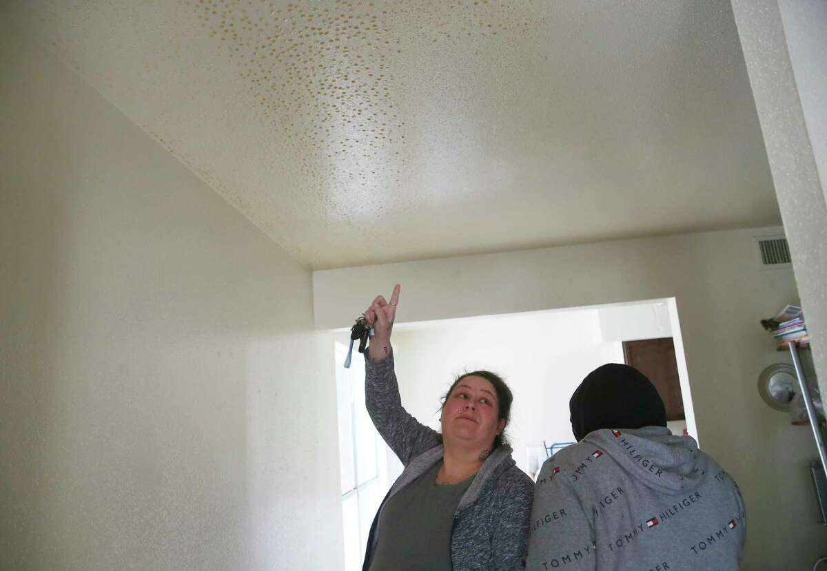 Brandy Robinson, 36, looks at mold growing on her ceiling of her Seven Oaks Apartments unit, Thursday, Feb. 18, 2021. Her unit flooded after a water pipe to the water heater busted causing damage to most of her belongings on Monday during the extreme cold spell. After two days of living in the flooded unit she was able get a room at the Best Western Hotel off Loop 410. With only Social Security and food stamps, she is pleading with friend for help in paying for the hotel room and is not sure how much longer they can stay. Along with her daughter, Cierra Arceneaux, 18, they were trying to salvage as much of their clothing as possible.