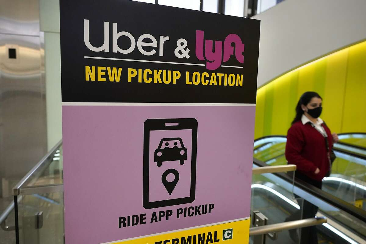 A passer-by walks past a sign offering directions to an Uber and Lyft ride pickup location at Logan International Airport, in Boston. Trump administration rules that would make it easier to classify workers as independent contractors, like Uber and Lyft drivers, have been blocked by President Biden's Labor Department.