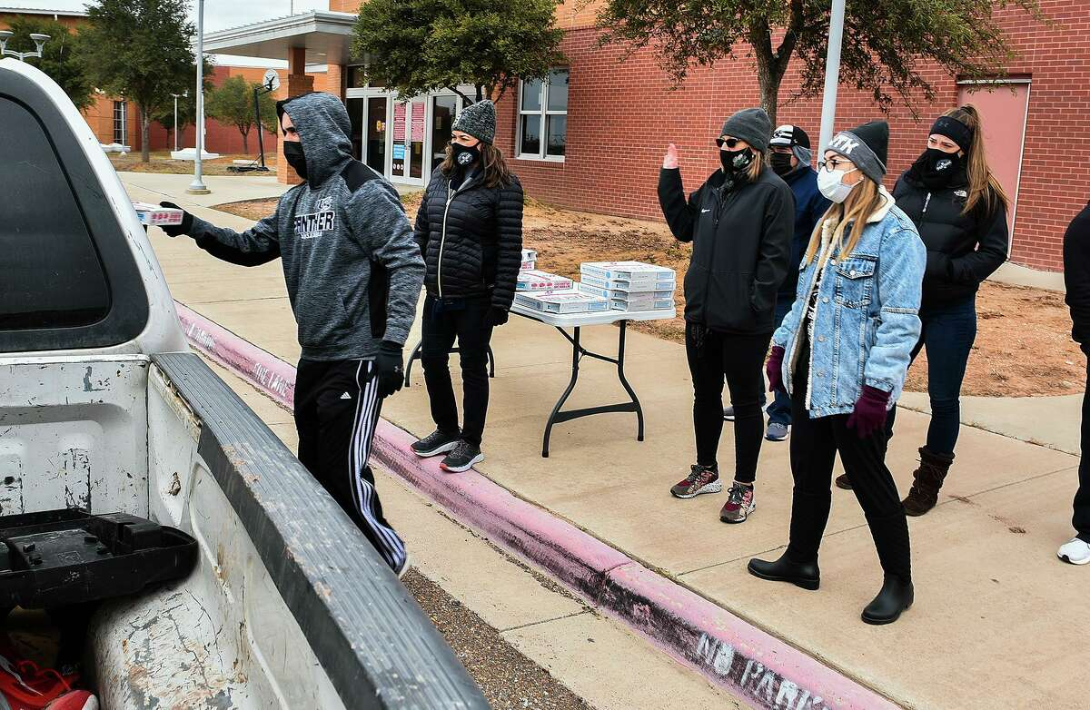 United South High School administrators hand out free pizza to families in need on Thursday, Feb. 18 outside the Juvenile Justice Alternative Education Program Center.