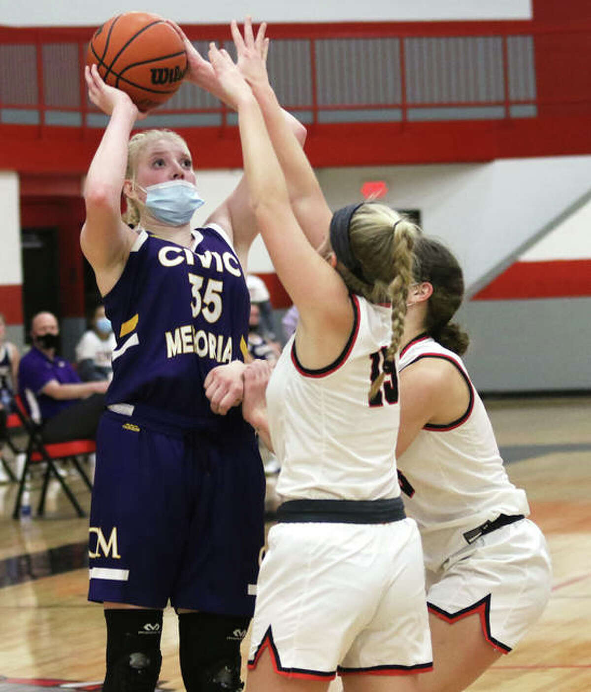 CM's Claire Christeson (left) shoots over Highland's Grace Wilke (15) and Bella LaPorta on Thursday night in Highland.