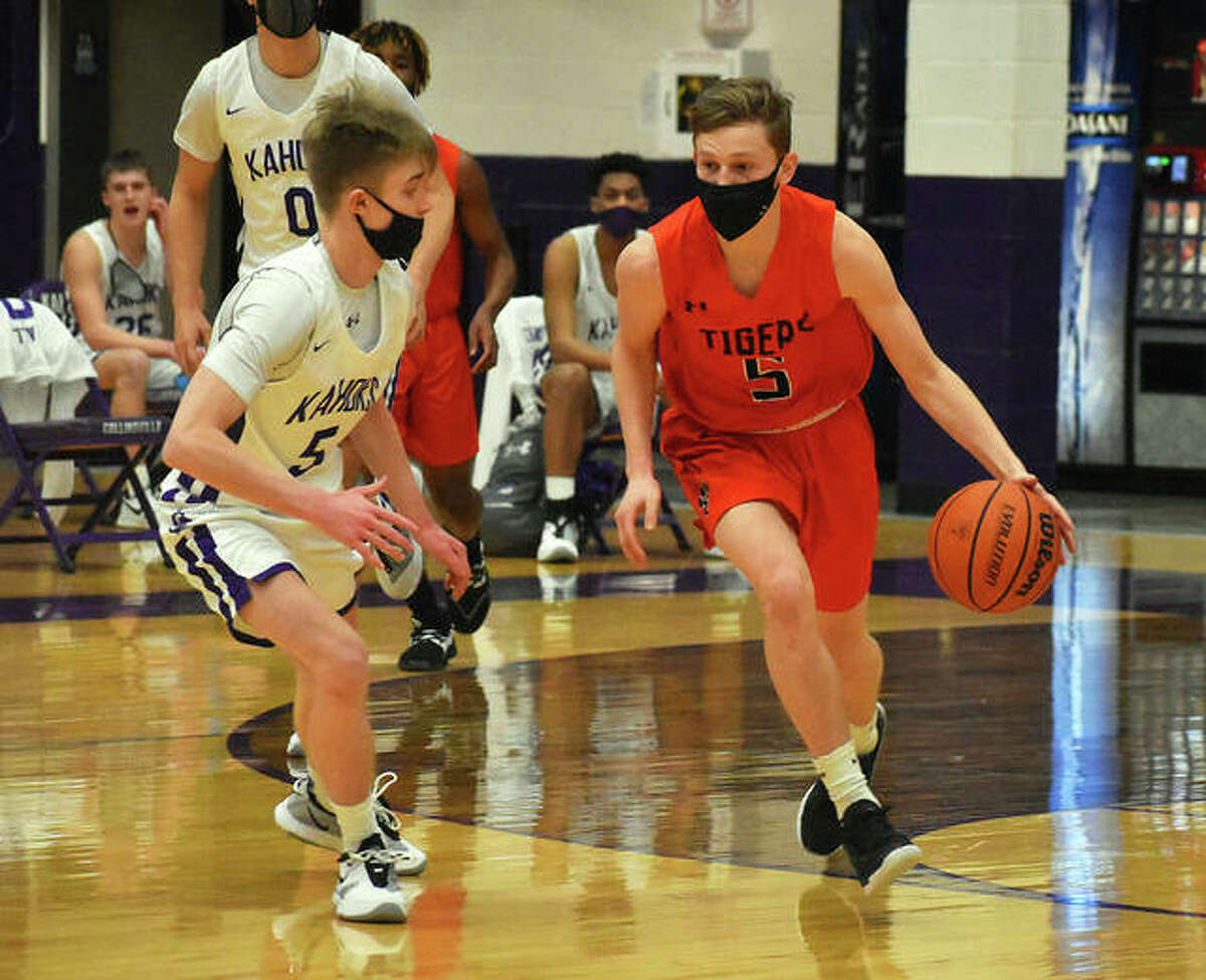 Edwardsville's Preston Weaver, right, dribbles the ball up the court while facing pressure from a Collinsville defender on Thursday.