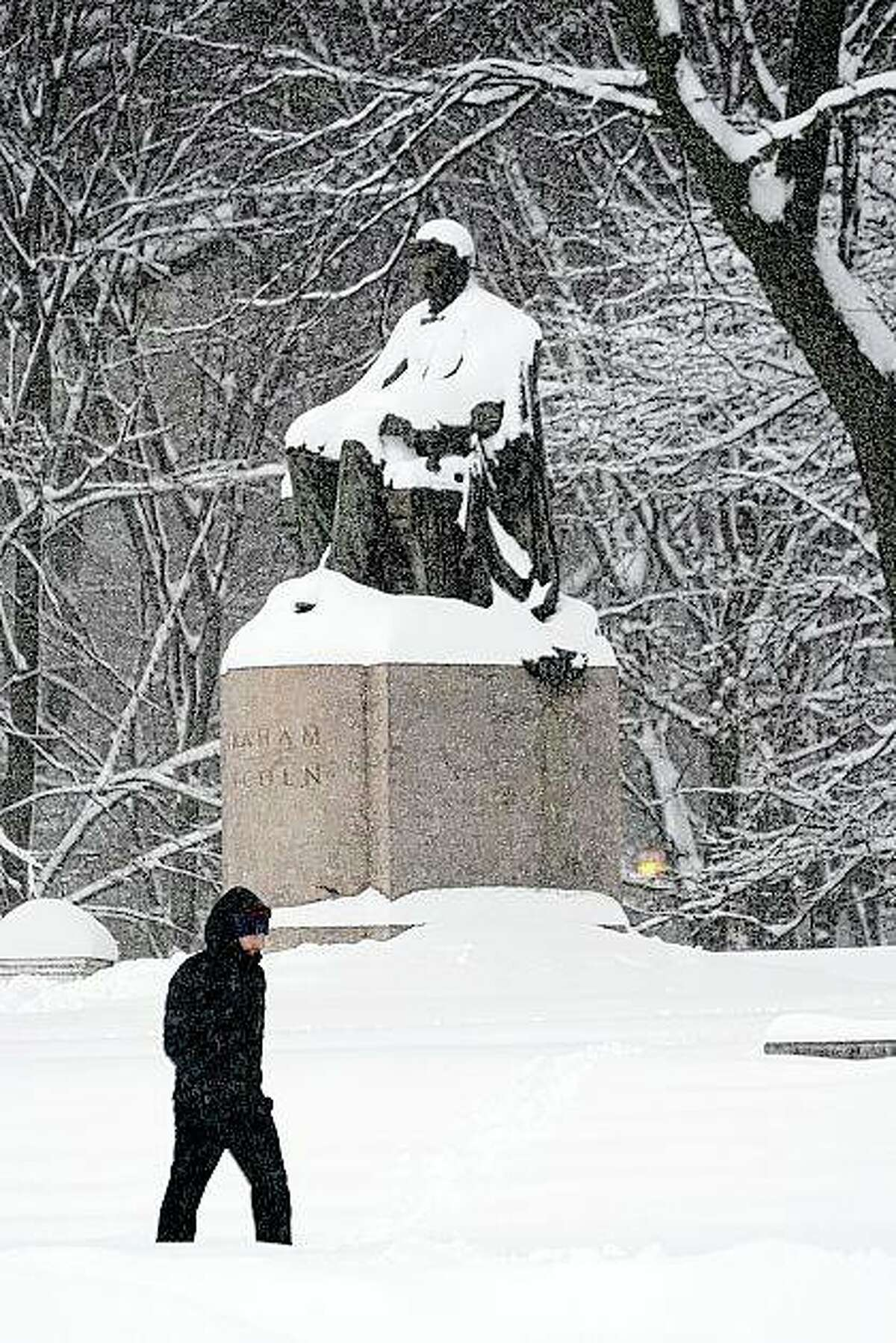 A lone man walks in January past a snow-covered statue of Abraham Lincoln in Chicago's Grant Park. A committee is considering the future of Lincoln statues in the city.