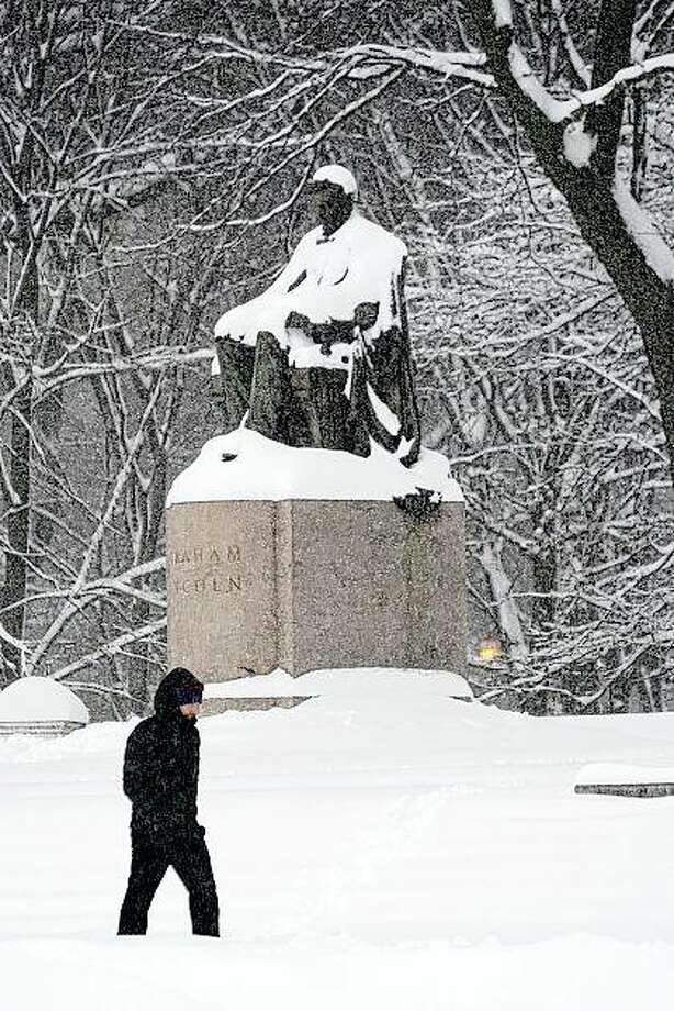 A lone man walks in January past a snow-covered statue of Abraham Lincoln in Chicago's Grant Park. A committee is considering the future of Lincoln statues in the city. Photo: Charles Rex Arbogast | Associated Press