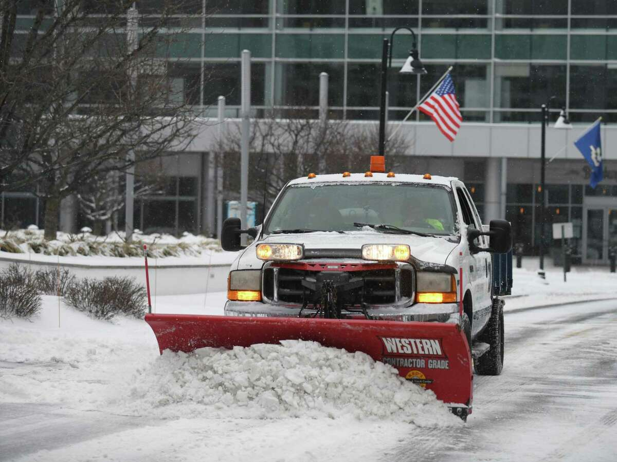 A plow clears snow at Harbor Point in Stamford, Conn. Thursday, Feb. 18, 2021. The area received a blanketing of snow starting Thursday morning that is expected to last into Friday.