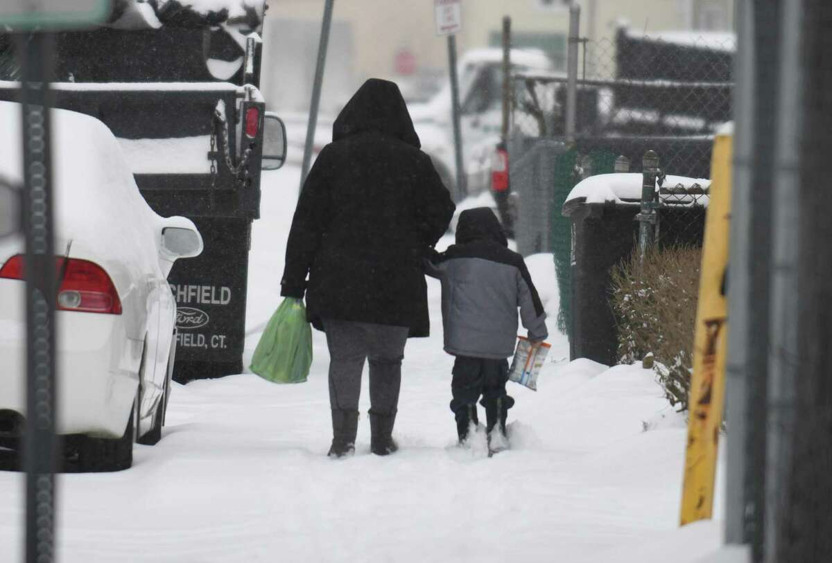 A mother and child walk in the snow in the South End of Stamford, Conn., on Thursday, Feb. 18, 2021.