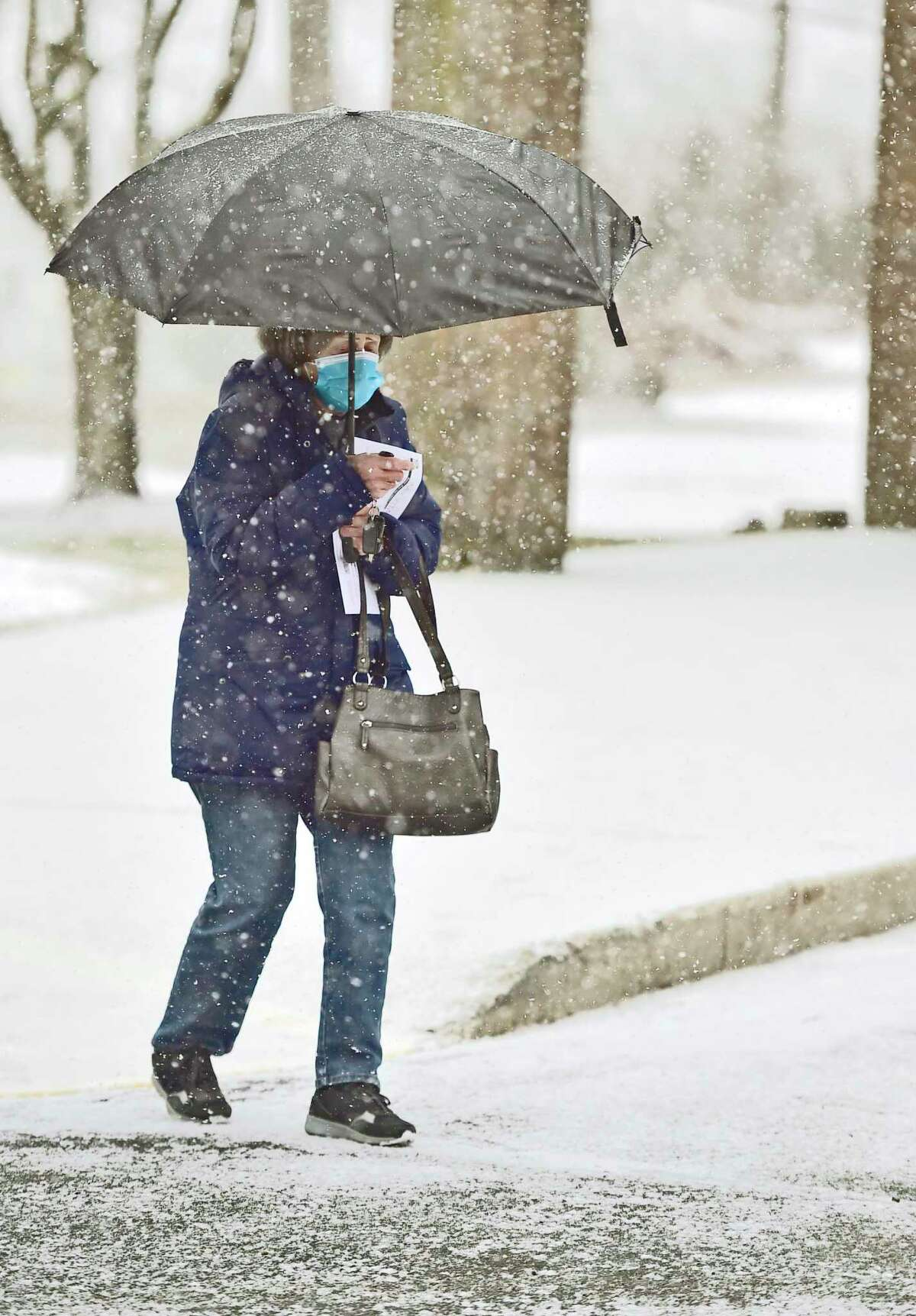 Rose Marie Gangone of Clinton shields herself from the snow with an umbrella as she leaves the Henry Carter Hull Library in Clinton Thursday morning.