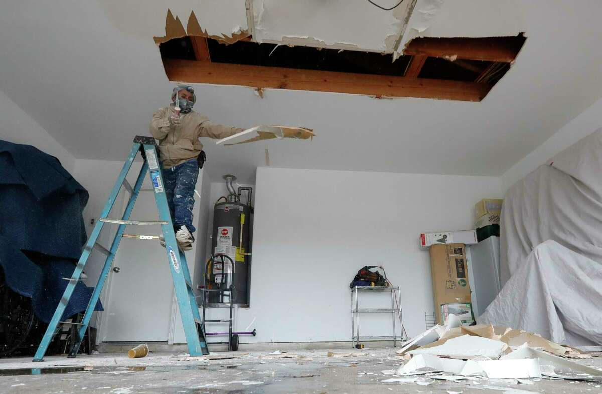 Manyu Torres stripes out Sheetrock after a women's pip burst above her garage, damaging her car, roof and ceiling on Feb. 18. Some Montgomery County residents could see some relief on their property taxes if their home was damaged during the winter storm that blew through Texas Feb. 12.