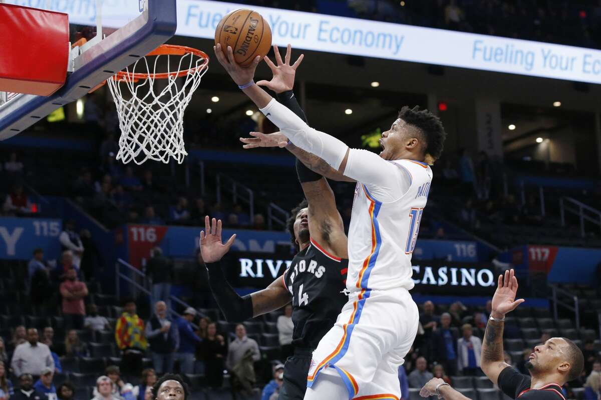 Oklahoma City Thunder center Justin Patton, center, goes to the basket in front of Toronto Raptors forward Rondae Hollis-Jefferson (4) during the second half of an NBA basketball game Wednesday, Jan. 15, 2020, in Oklahoma City. (AP Photo/Sue Ogrocki)
