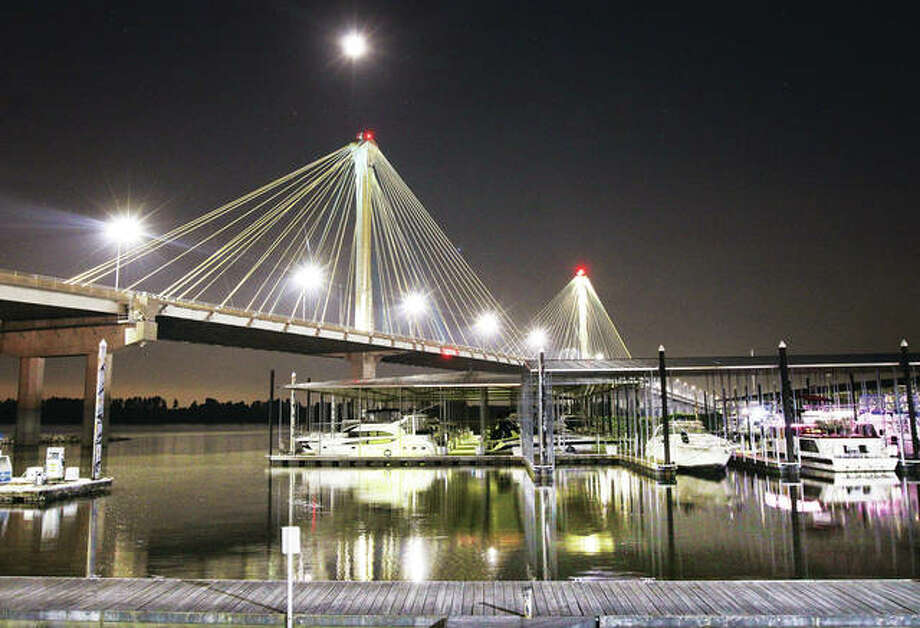 The half-moon shines high over the Clark Bridge and the calm waters of the Alton Marina last summer. Tourism advocates in Illinois this week called upon the state to create a plan for post-pandemic recovery for hotels, attractions and restaurants.