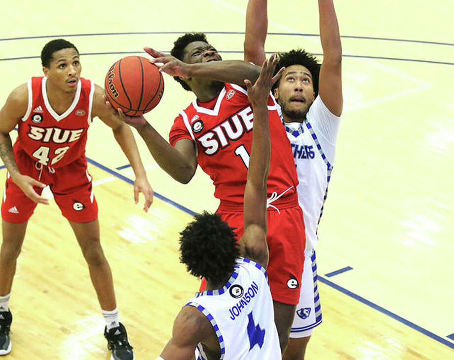 SIUE's Mike Adewunmi (1), shown putting up a shot between Eastern Illinois defenders Jan. 26 in Charleston, scored 17 points Thursday night when the Cougars were back on the road at Clarksville, Tenn., in an OVC loss to Austin Peay. Photo: Greg Shashack / The Telegraph