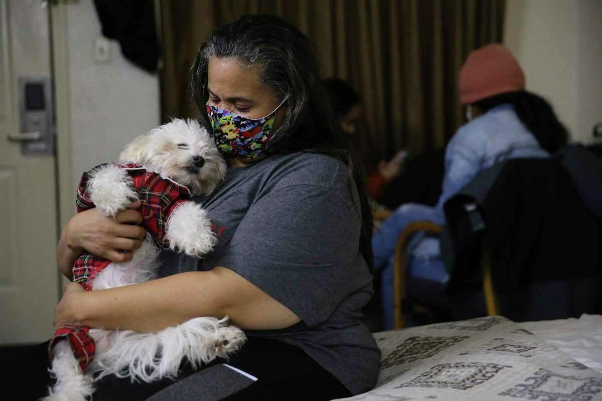 Ginette Palmer cuddles her family pet, Major, as her husband, Eddie, undergoes peritoneal dialysis at a motel on Wednesday, Feb. 18, 2021.