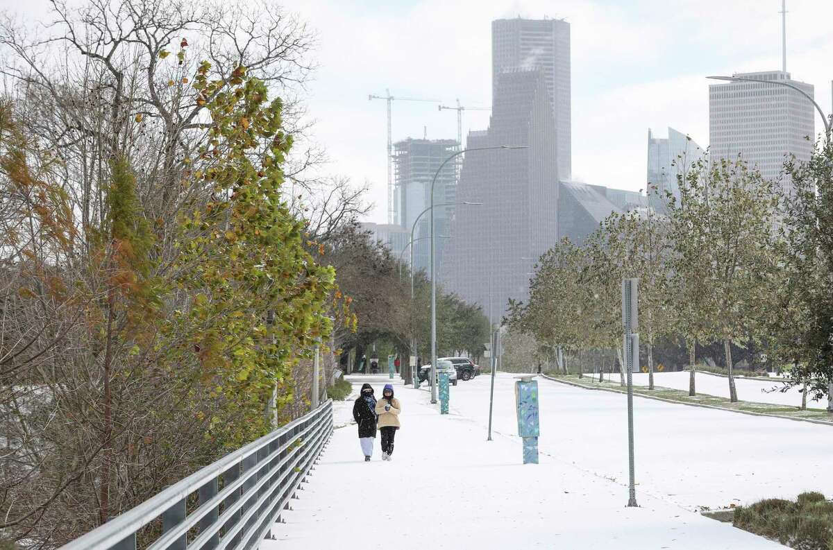 Two women walk along Allen Parkway as a winter storm hits Houston on Monday, Feb. 15, 2021, at Buffalo Bayou Park in Houston.