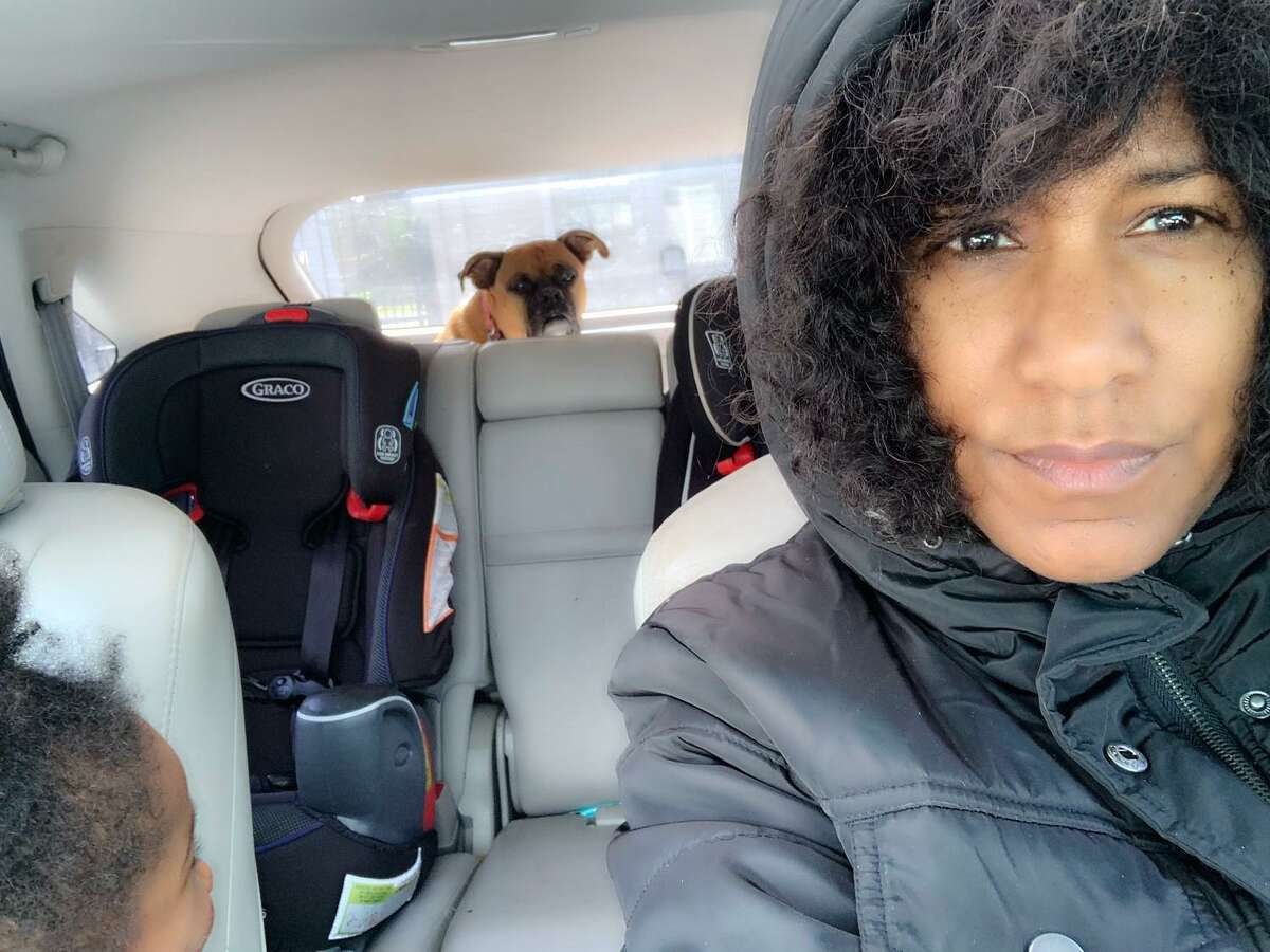 The Houston Chronicle's Joy Sewing warms up in the car with her children and dogs during the arctic blast.