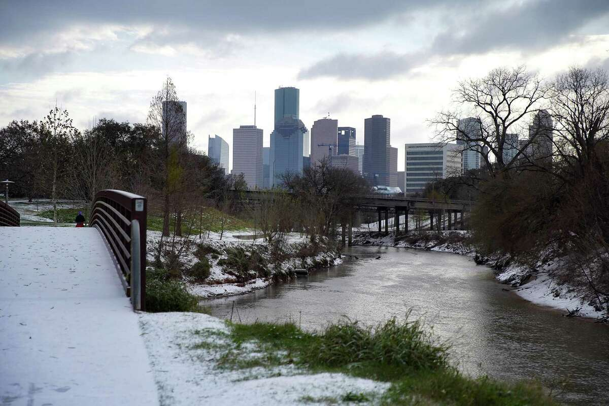 Snow accumulates Monday along Buffalo Bayou. But an enchanting winter wonderland it was not, as millions were left without power.