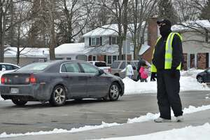 Parents and guardians arrive at Chestnut Hill Elementary school in Midland to pick up their children around 3:30 p.m. in the afternoon on Thursday, Feb. 19, 2021. With help from Parent Volunteer Todd Meyers, traffic runs smoothly and efficiently. (Ashley Schafer/ashley.schafer@hearstnp.com)