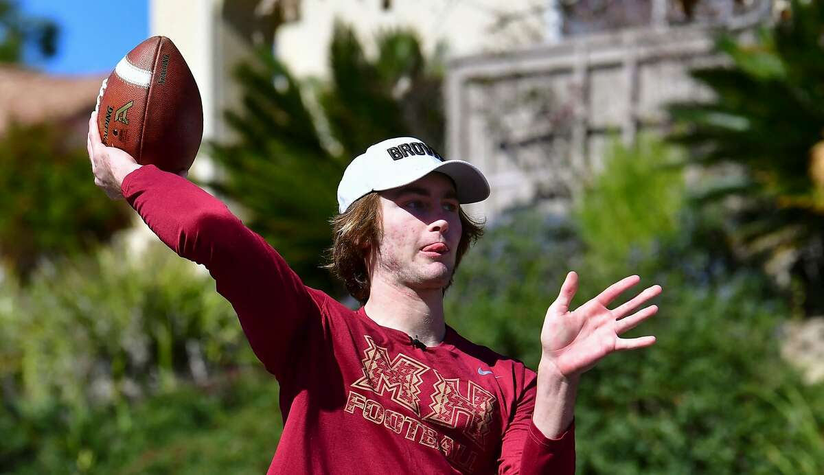 High school football quarterback Gunnar Hensley throws a pass to his father Brad on streets near their home in Carlsbad.