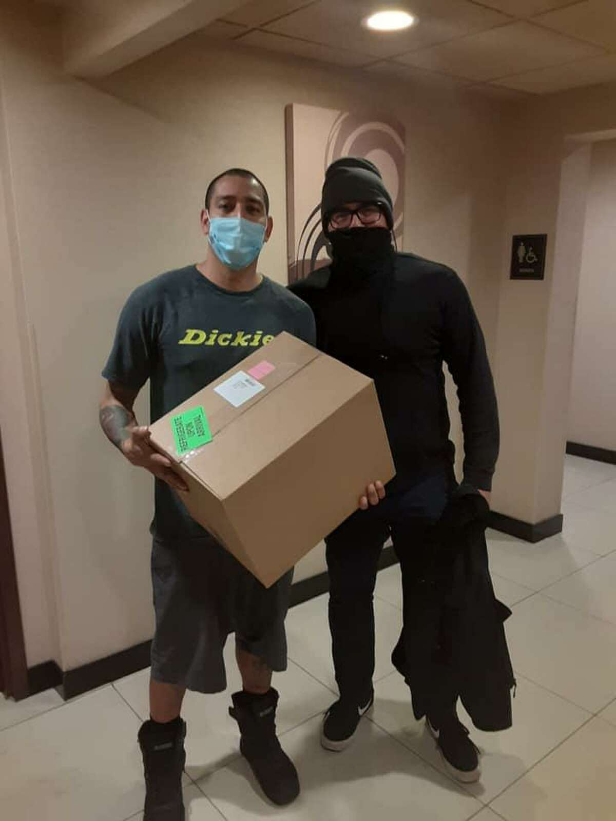 Atlas Delivery Service driver Pablo Pedraza, 40, left, stands with Reynaldo Villegas, after driving from Houston to San Antonio, through bad weather and on icy roads, to deliver life-saving medicine for Villegas' baby daughter, Evangelina.