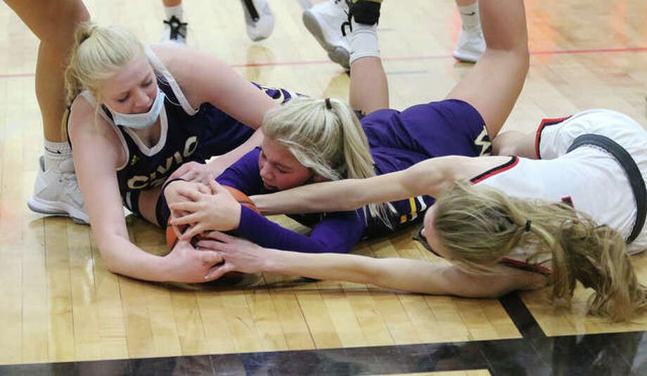 CM's Kelbie Zupan (middle) is first to the floor for a loose ball that attracts teammate Claire Christeson (left) and Highland's Lydia Hadowsky in the second half Thursday night in Highland. Photo: Greg Shashack / The Telegraph