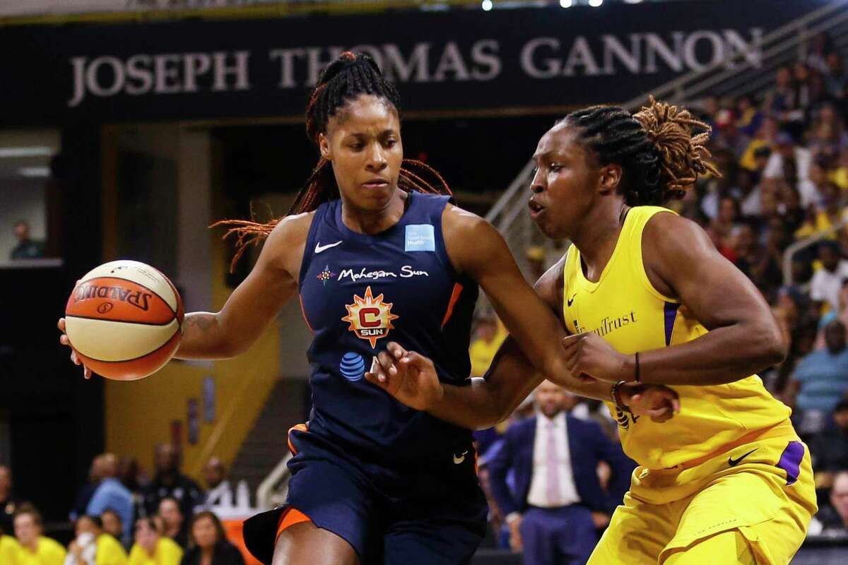 The Connecticut Sun's Bria Holmes, left, drives against the Los Angeles Sparks' Chelsea Gray during the first half of Game 3 of a WNBA playoff game in 2019.