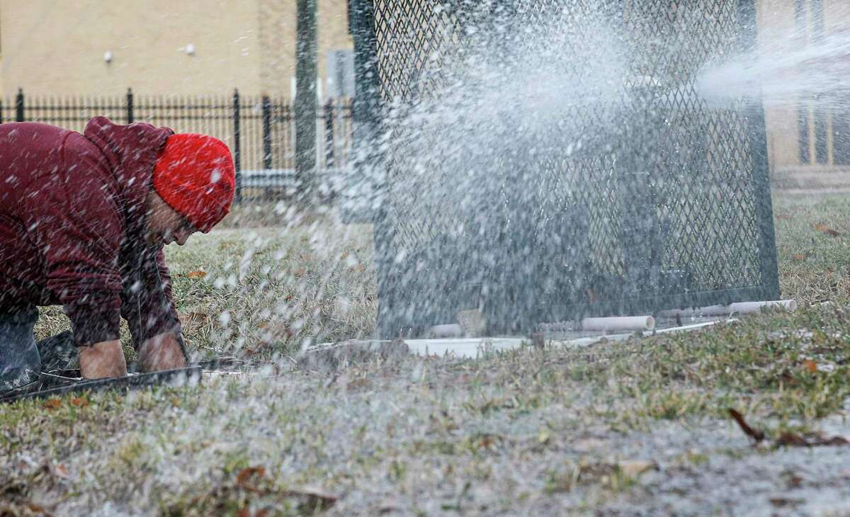 Octavio Jovellano, a maintenance workers, turns off water in a building at the intersection of Lyons Avenue and Waco Street on Thursday. The city has received 4,900 reports of burst pipes, but the true toll is likely much higher.
