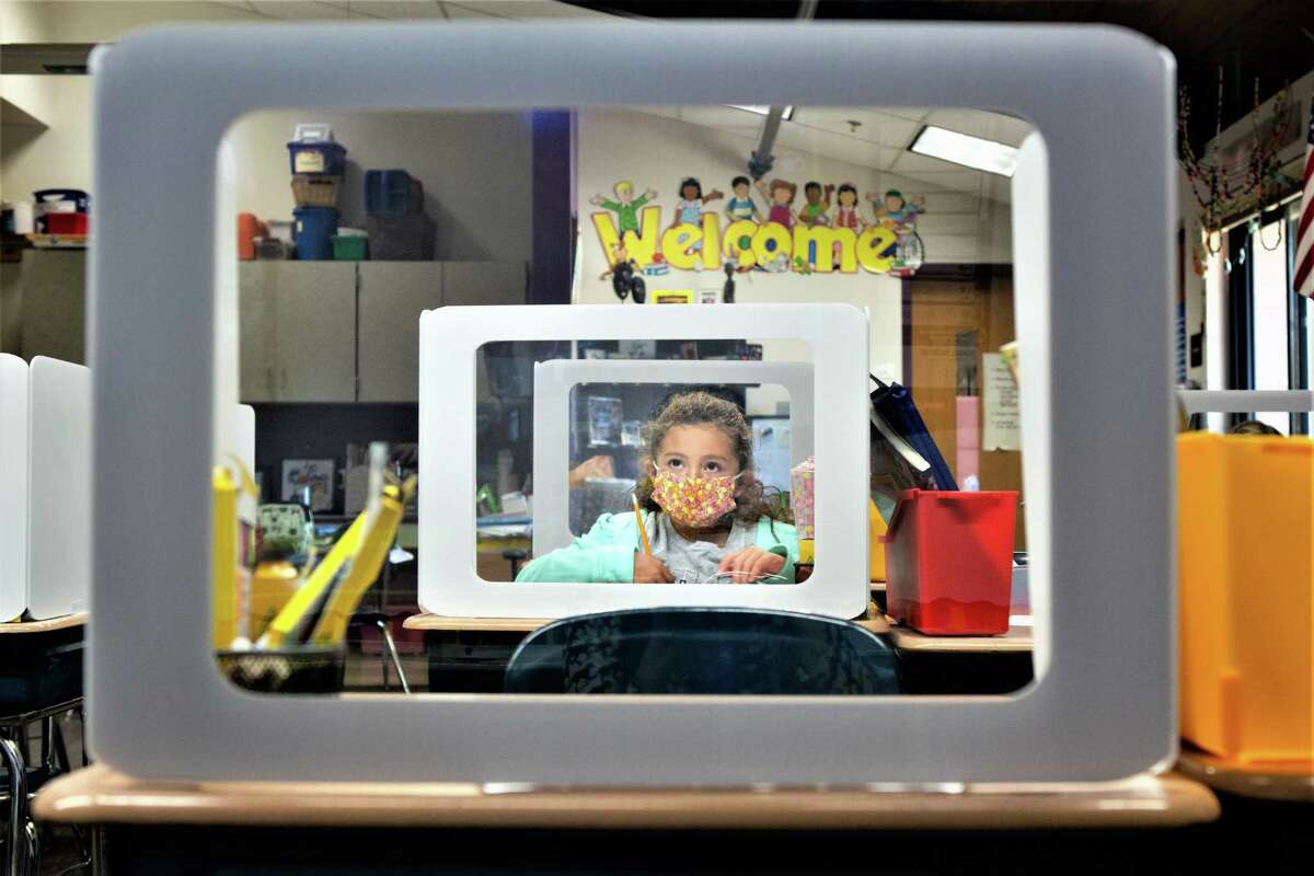 A second-grade student works behind a protection shield at a socially distanced desk at Wesley Elementary School in Middletown.