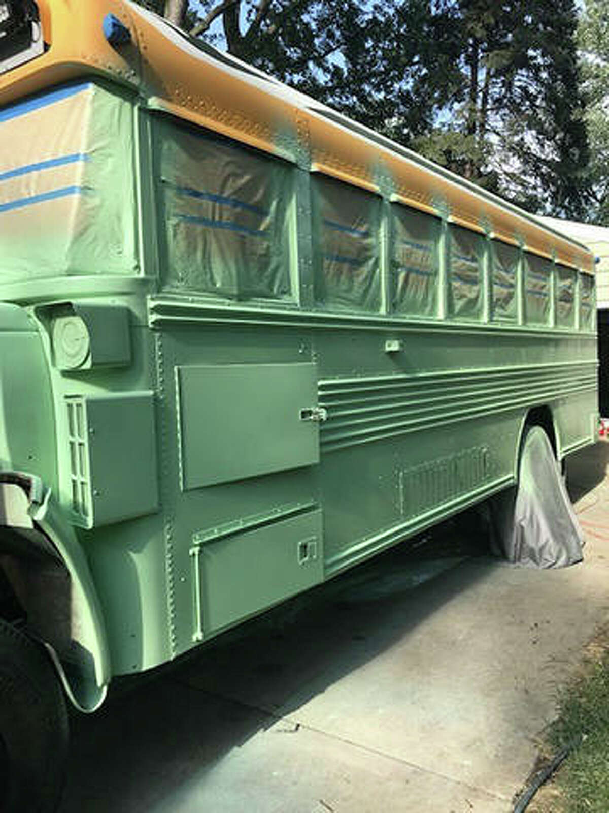 """A photo of the """"Skoolie,"""" a refitted school bus built by Lana and Mark Maue of Edwardsville, as it was being painted green."""