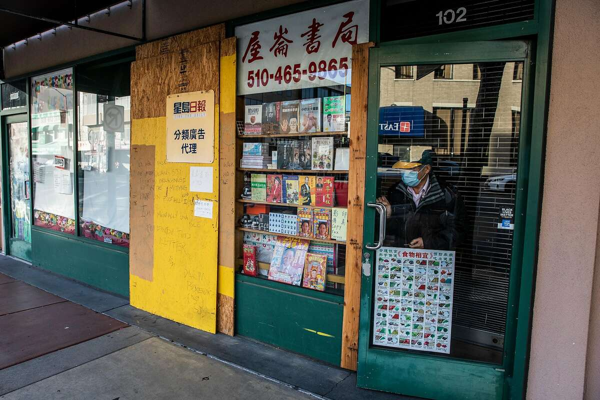 Owner Daniel Wong closes the partially barricaded Oakland Chinese Book Store.