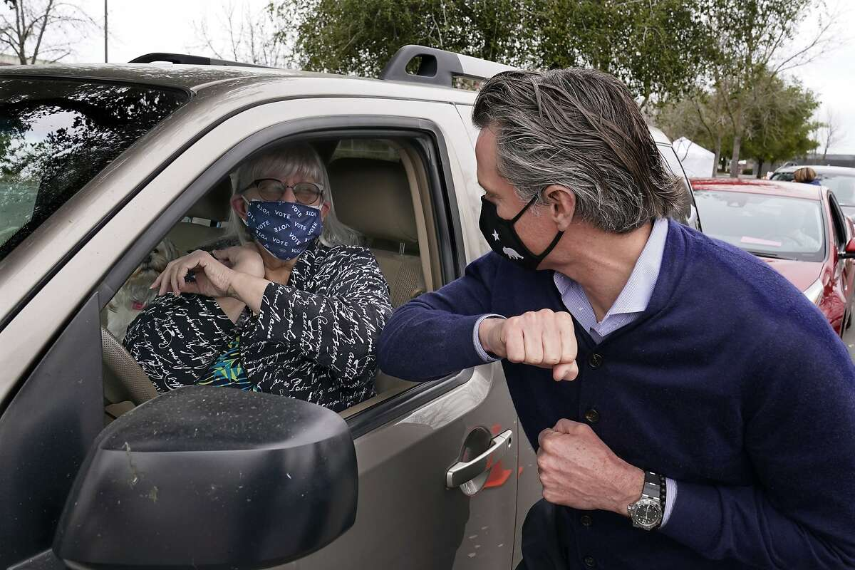 Gov. Gavin Newsom gives an elbow bump to a woman waiting to get a coronavirus vaccination in Sacramento on Feb. 11. Newsom said Friday that 10% of coronavirus vaccines would be set aside for teachers and other education workers in California.