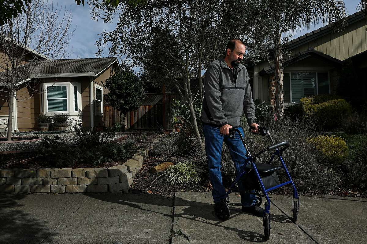 Fred Marziano, 50, a Marin County Sheriff's deputy, poses for a portrait on Thursday, January 18, 2021, in Petaluma, Calif. Marziano got COVID-19 last March -- and the symptoms never went away. He was an athletic guy, and now he uses a walker that he named Wally. He got sick at the same time as Matt Willis, the Marin County public health director, who's 54. Willis returned to work in April. Marziano just announced his retirement.